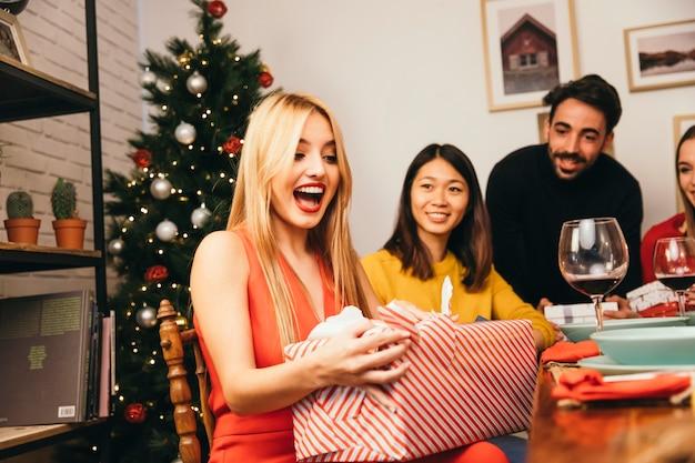Mujer riendo abriendo caja de regalo en cena de navidad