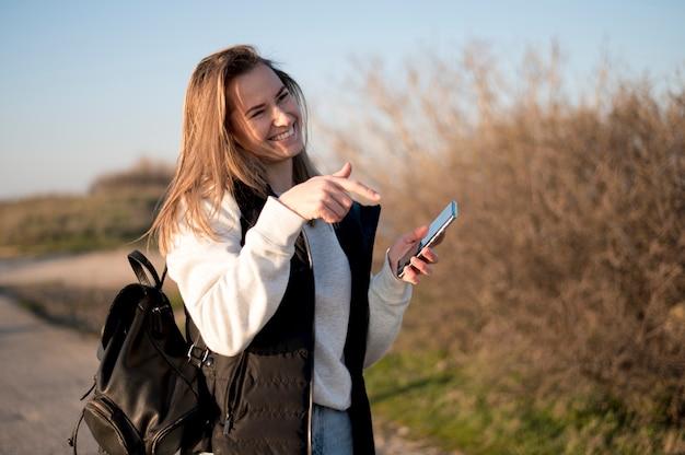 Mujer riendo y apuntando a su teléfono