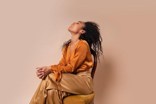 Mujer riendo con cabello rizado perfecto en elegante blusa naranja y pantalones de seda sentado en silla vintage