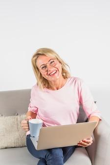 Mujer riendo envejecida en blusa rosa con laptop y taza en sofá