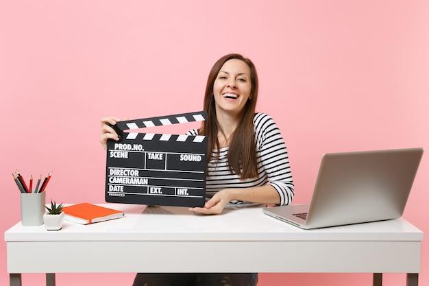 Mujer riendo sosteniendo claqueta de cine negro clásico, trabajando en un proyecto mientras se sienta en la oficina con la computadora portátil