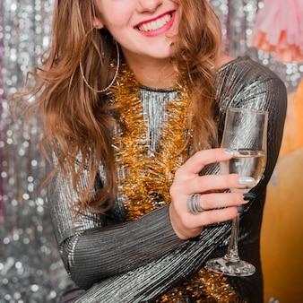Mujer riendo en traje de noche con vaso de bebida