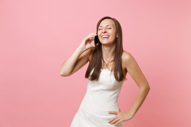 Mujer riendo en vestido blanco hablando por teléfono móvil, llevando una conversación agradable