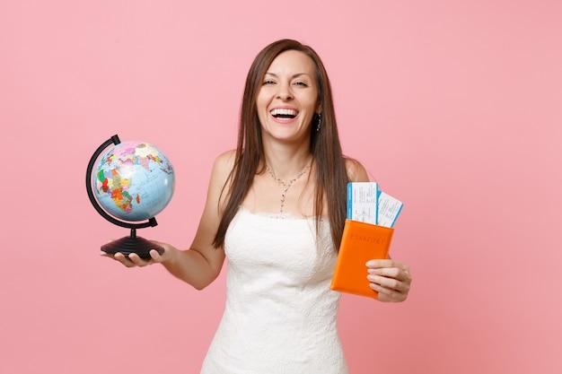 Mujer riendo en vestido blanco sosteniendo globo terráqueo, pasaporte boleto de embarque para ir al extranjero, vacaciones