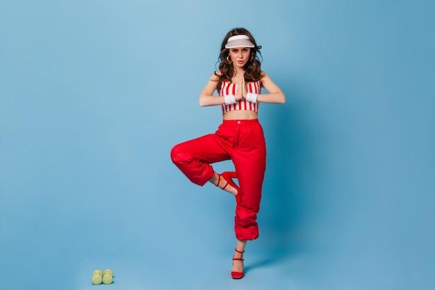 Mujer rizada activa en gorra blanca y traje rojo de pie en pose de árbol