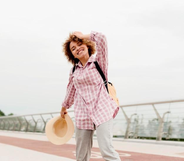 Mujer rizada de ángulo bajo disfrutando de sus vacaciones