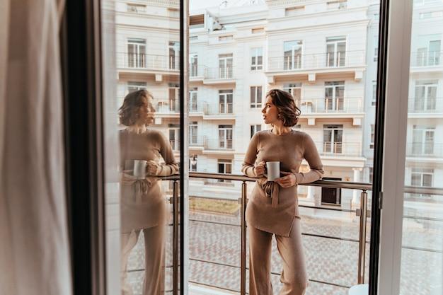 Mujer rizada bien vestida de pie junto a la ventana grande con café. foto de hermosa dama caucásica disfrutando de un té y mirando a la calle.