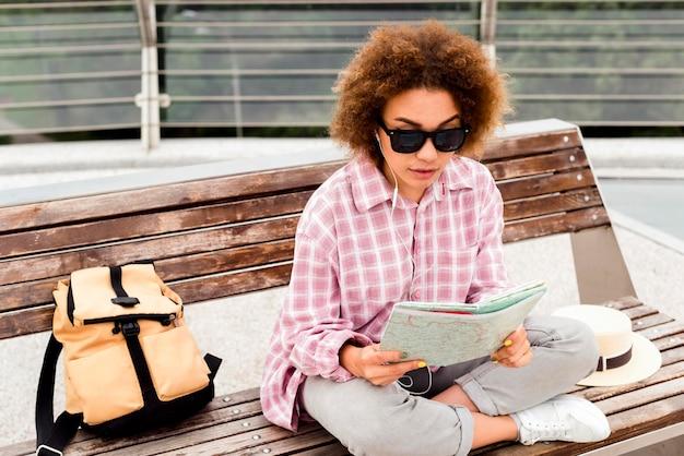 Mujer rizada comprobando su mapa en un banco