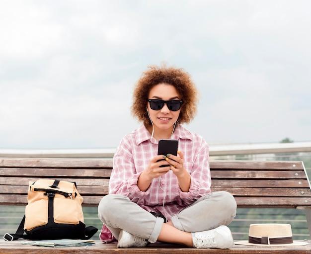 Mujer rizada comprobando su teléfono en un banco