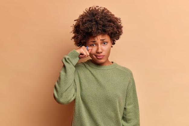 La mujer rizada desanimada decepcionada limpia las lágrimas se encuentra estresada con expresión sombría vestida con un vestido naranja de moda posa contra la pared azul