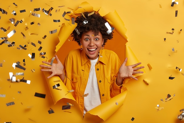 Mujer rizada emocionada por muchas ventas que comenzaron en el centro comercial, fascinada por noticias increíbles, extiende las palmas y sonríe con dientes