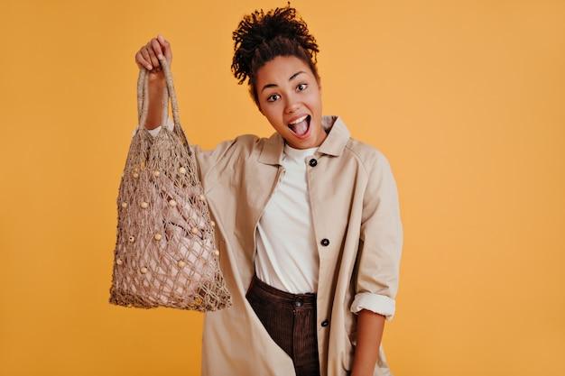 Mujer rizada emocional sosteniendo bolsa de hilo