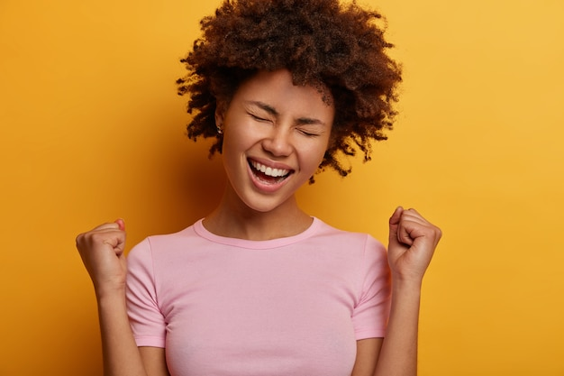 La mujer rizada eufórica hace un gesto de sí, aprieta los puños, está emocionada por una gran noticia, celebra la victoria, tiene una expresión de alegría, tiene un premio, inclina la cabeza, posa y hace gestos contra la pared amarilla