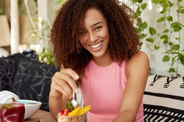 Mujer rizada con expresión alegre, come delicioso postre, está de buen humor, pasa tiempo libre en una acogedora cafetería, disfruta de una sabrosa ensalada de frutas. atractiva hembra descansa después de una excursión sola
