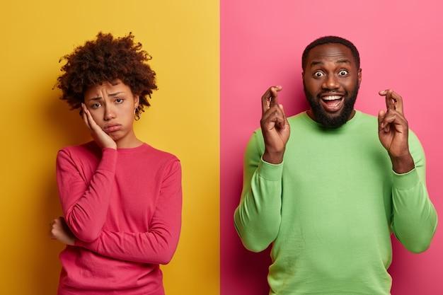 La mujer rizada de fatiga molesta se ve triste, su novio está feliz cerca, mantiene los dedos cruzados, cree en la buena fortuna, usa un jersey verde, se para contra la pared amarilla y rosa