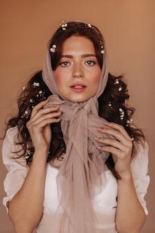 Mujer rizada con flores en el pelo atado bufanda en arco y mirando a cámara.
