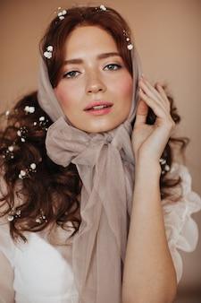 Mujer rizada de jengibre en pañuelo beige y flores en el cabello mira suavemente a la cámara.