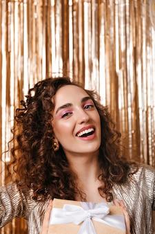 Mujer rizada de ojos grises sonriendo sobre fondo dorado
