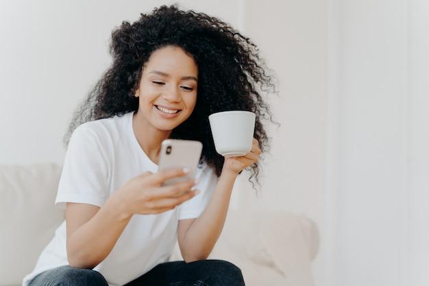 Mujer rizada pacífica con teléfono inteligente, bebe café, posa en el sofá de la sala de estar, recibe una oferta de trabajo bien remunerada