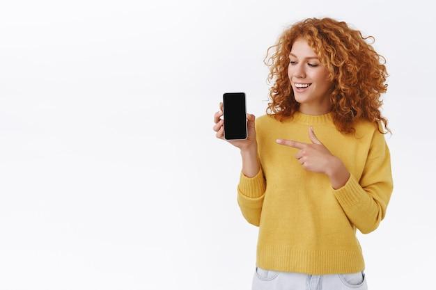 Mujer rizada pelirroja atractiva complacida en suéter amarillo, sosteniendo un teléfono inteligente, señalando la pantalla móvil y sonriendo, recomienda la aplicación, pared blanca