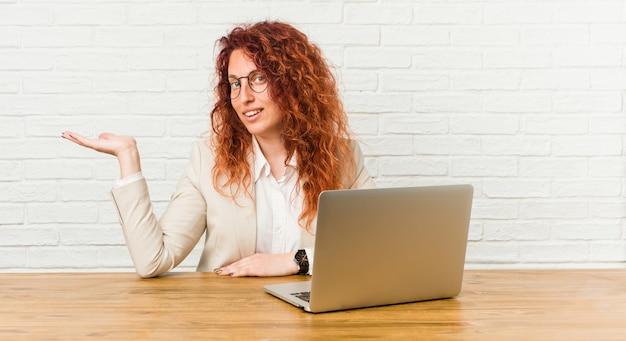 Mujer rizada pelirroja joven que trabaja con su computadora portátil que muestra un espacio de la copia en una palma y que sostiene otra mano en la cintura.