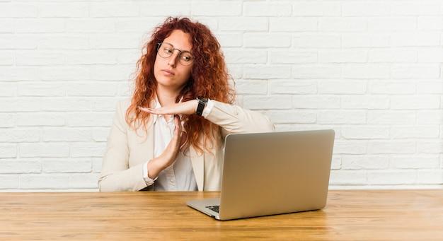 Mujer rizada pelirroja joven que trabaja con su computadora portátil que muestra un gesto de tiempo de espera.