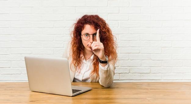 Mujer rizada pelirroja joven que trabaja con su computadora portátil que muestra el número uno con el dedo.