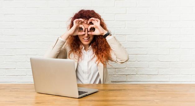 Mujer rizada pelirroja joven que trabaja con su computadora portátil que muestra signo bien sobre los ojos