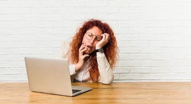 Mujer rizada pelirroja joven que trabaja con su computadora portátil quejándose y llorando desconsoladamente.
