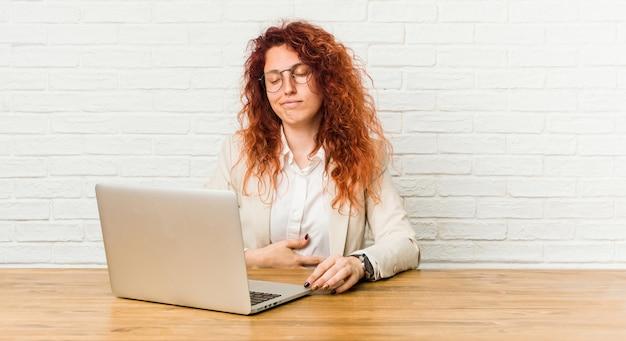 La mujer rizada pelirroja joven que trabaja con su computadora portátil toca la panza, sonríe suavemente