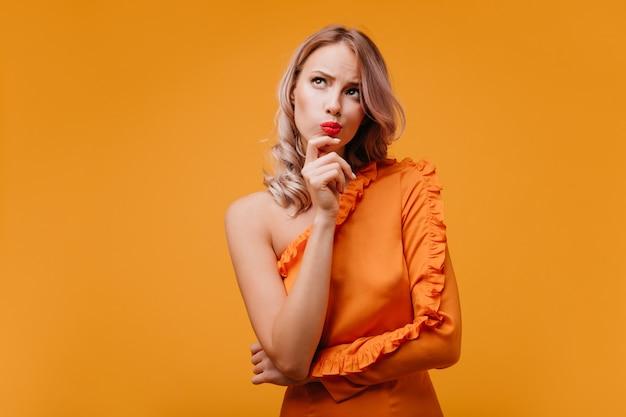 Mujer rizada pensativa en vestido naranja mirando hacia arriba