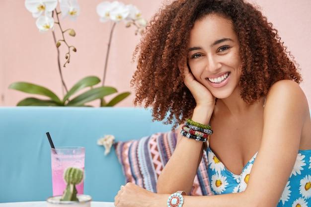 Mujer rizada de piel oscura positiva con amplia sonrisa disfruta de una buena recreación en la cafetería, bebe cócteles mientras se sienta en un cómodo sofá