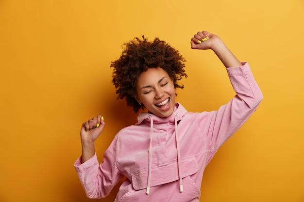 La mujer rizada de piel oscura positiva mantiene las manos levantadas en el aire, baila sin preocupaciones, se siente vivaz y optimista, usa una sudadera con capucha de terciopelo, aislada sobre una pared amarilla, lanza una fiesta, disfruta de la libertad