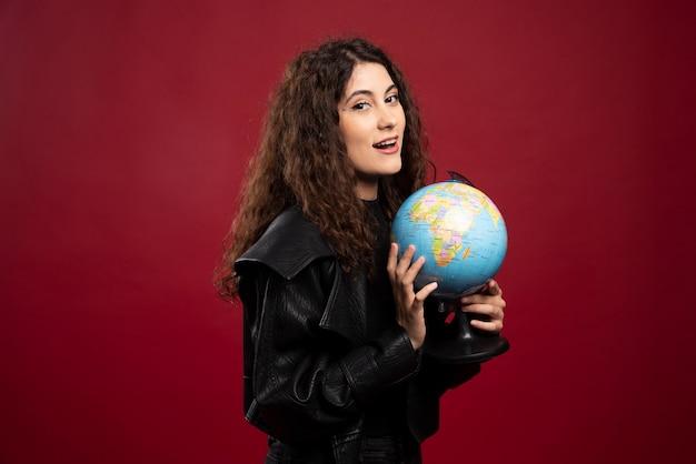 Mujer rizada posando con globo.