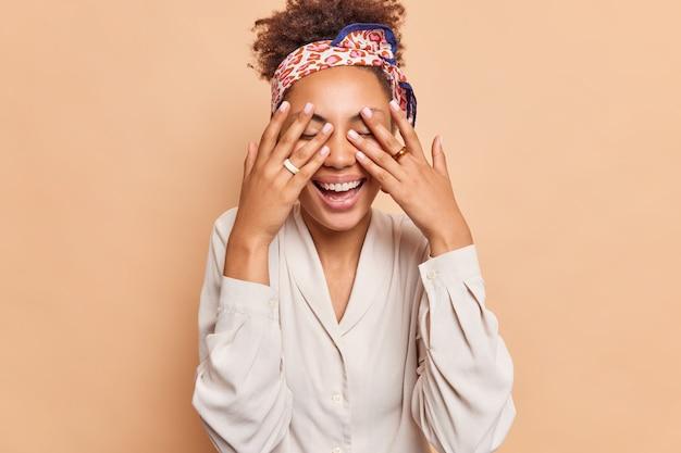 La mujer rizada positiva cubre los ojos sonríe ampliamente espera la sorpresa tiene una manicura perfecta, incluso los dientes usan anillos en los dedos, diadema y camisa blanca aislada sobre una pared marrón