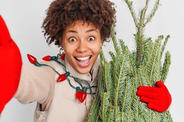 La mujer rizada positiva excesiva estira el brazo hace que la selfie sonríe en general, siendo muy feliz después de comprar un abeto de hoja perenne recién cortado para el año nuevo que se prepara para las vacaciones de invierno. se acerca la navidad