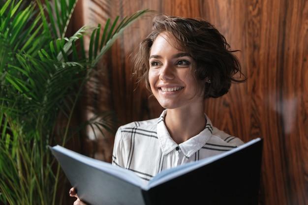 Mujer rizada sonriente con documentos