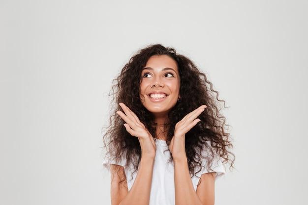 Mujer rizada sonriente con las manos cerca de la cabeza mirando hacia arriba