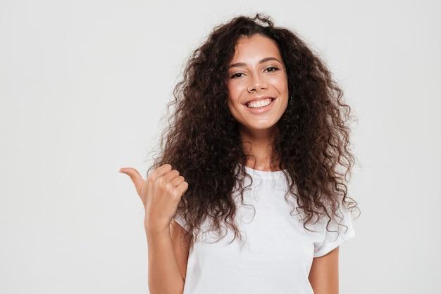Mujer rizada sonriente que muestra el pulgar para arriba