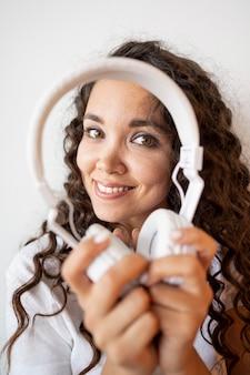 Mujer rizada sonriente que sostiene un par de auriculares