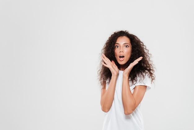Mujer rizada sorprendida cogidos de la mano cerca de la cabeza