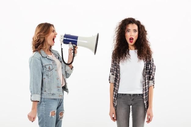 Mujer rizada sorprendida cubriendo sus oídos mientras la segunda niña le grita con megáfono sobre la pared blanca