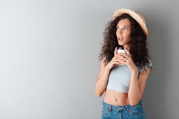 Mujer rizada sorprendida en sombrero tomando café y mirando a otro lado