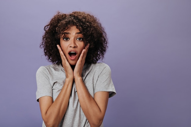 Mujer rizada con sorpresa mira al frente en la pared púrpura