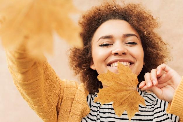 Mujer rizada sosteniendo hojas otoñales