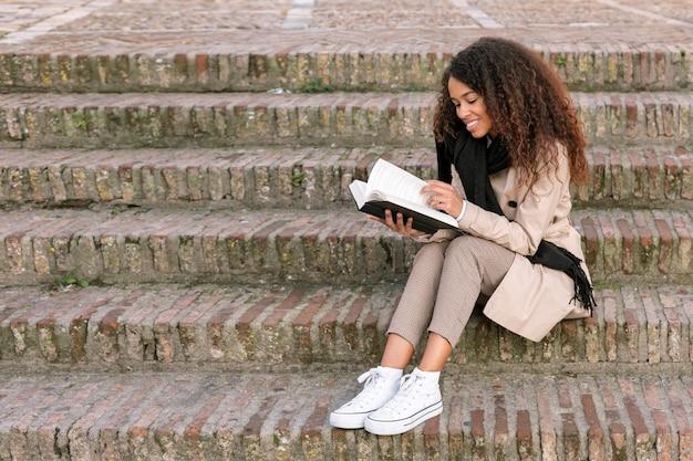 Mujer rizada de tiro largo que lee un libro