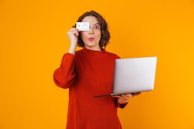 Mujer rizada vistiendo un suéter con una computadora portátil plateada y una tarjeta de crédito mientras está de pie aislado en amarillo
