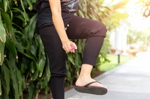 Mujer rociando picaduras de insectos mosquitos en su pierna