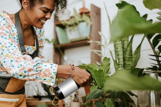 Mujer rociar las plantas con un spray de agua en una tienda de plantas