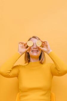 Mujer con rodajas de limón enfrente los ojos en un escenario amarillo